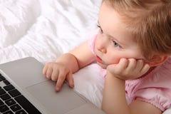 Petite fille avec l'ordinateur portatif Image libre de droits