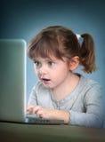 Petite fille avec l'ordinateur portatif Photo libre de droits