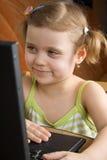 Petite fille avec l'ordinateur portatif images stock