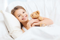 Petite fille avec l'ours de nounours dormant à la maison Photo stock