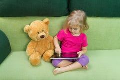 Petite fille avec l'ours de nounours, et un comprimé Images stock
