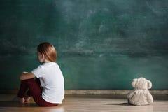 Petite fille avec l'ours de nounours se reposant sur le plancher dans la chambre vide Concept d'autisme Photo libre de droits