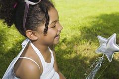 Petite fille avec la baguette magique magique d'étoile Photographie stock libre de droits