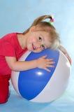 Petite fille avec la bille de plage. Photo stock