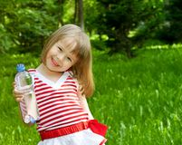 Petite fille avec la bouteille en plastique de l'eau minérale Image stock