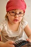 Petite fille avec la calculatrice Photo stock