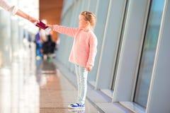 Petite fille avec la carte d'embarquement dans le vol de attente d'aéroport Images stock