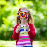 Petite fille avec la lucette colorée de sucrerie Images stock