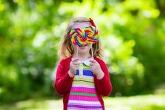 Petite fille avec la lucette colorée de sucrerie Photo stock