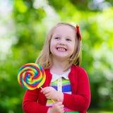 Petite fille avec la lucette colorée de sucrerie Photo libre de droits