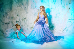 Petite fille avec la mère dans la robe de princesse sur un fond de W Photographie stock