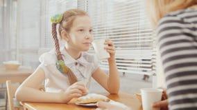 Petite fille avec la maman en café - l'ado explique quelque chose pour la mère images stock