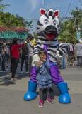 Petite fille avec la mascotte de zèbre Photo libre de droits
