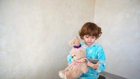 Petite fille avec la musique de écoute d'ami au téléphone Photographie stock libre de droits