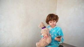 Petite fille avec la musique de écoute d'ami au téléphone Photographie stock