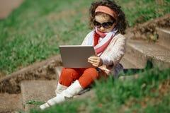 Petite fille avec la tablette image stock