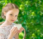 Petite fille avec la tasse blanche extérieure photographie stock