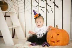 Petite fille avec la trisomie 21 se reposant avec un balai près du grand potiron Images stock