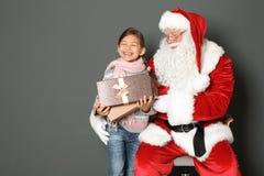 Petite fille avec le boîte-cadeau et la Santa Claus authentique sur le fond gris images libres de droits