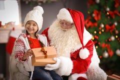 Petite fille avec le boîte-cadeau se reposant sur le ` authentique de Santa Claus photo stock