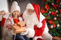 Petite fille avec le boîte-cadeau se reposant sur le ` authentique de Santa Claus photos stock