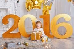 Petite fille avec le cadeau pendant la nouvelle année 2016 Photographie stock libre de droits