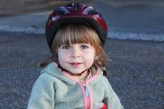 Petite fille avec le casque faisant du vélo Photo libre de droits