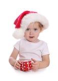 Petite fille avec le chapeau de Santa et le cadre de cadeau rouge Photographie stock libre de droits