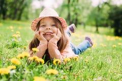 Petite fille avec le chapeau se trouvant sur l'herbe Photos stock
