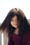 Petite fille avec le cheveu balayé par le vent brun Image stock
