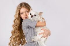 Petite fille avec le chien blanc de chiwawa sur le fond blanc Amitié d'animal familier d'enfants Photographie stock