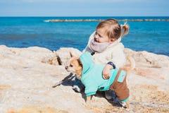 Petite fille avec le chien de chiwawa sur le bord de la mer, été extérieur Image stock