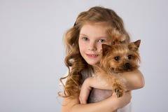 Petite fille avec le chien de Yorkshire Terrier d'isolement sur le fond gris Amitié d'animal familier d'enfants Images libres de droits