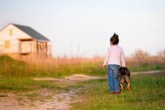 Petite fille avec le chien marchant dans la campagne Photo libre de droits