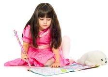 Petite fille avec le crayon se trouvant sur l'étage. d'isolement Images stock