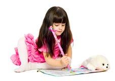 Petite fille avec le crayon se trouvant sur l'étage. d'isolement Photos stock