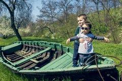 Petite fille avec le frère ayant l'amusement dans un vieux bateau extérieur Image stock