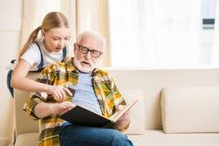 Petite fille avec le grand-père dans le livre de lecture de lunettes ensemble Photos stock