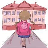 Petite fille avec le grand sac d'école se tenant vers le bâtiment scolaire Photo libre de droits