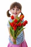 Petite fille avec le groupe de tulipes rouges Images stock