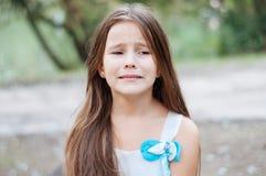 Petite fille avec le long portrait, pleurer avec émotion et le renversement de cheveux, éclairage naturel dehors photos libres de droits