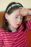 Petite fille avec le mal de tête Photos stock