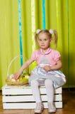 Petite fille avec le panier avec des oeufs de pâques Photographie stock