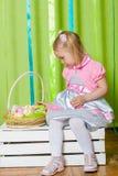 Petite fille avec le panier avec des oeufs de pâques Photos stock