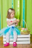 Petite fille avec le panier avec des oeufs de pâques Image stock