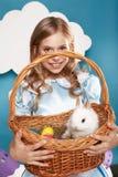 Petite fille avec le panier avec les oeufs de couleur et le lapin de Pâques blanc Images libres de droits