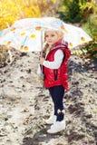 Petite fille avec le parapluie dans le gilet rouge extérieur Photographie stock libre de droits