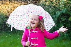 Petite fille avec le parapluie sous la pluie Photographie stock