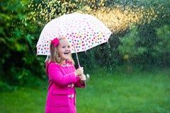Petite fille avec le parapluie sous la pluie Photographie stock libre de droits