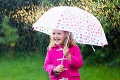 Petite fille avec le parapluie sous la pluie Photos libres de droits